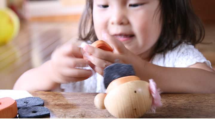 つぃくつぁく・ばんぴー(木のおもちゃ・ひも通し)で遊ぶ子供